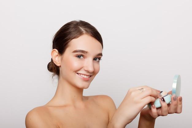 健康、人、美容のコンセプト-パウダーパフ、スキンケアのコンセプト、白い壁に隔離されたブルネットの少女の写真の構成で彼女の顔にほお紅を適用する若い女性