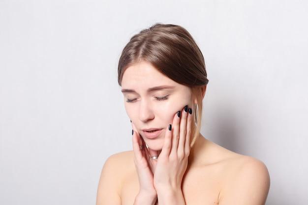 健康、人々、歯科およびライフスタイルの概念-歯の問題。歯の痛みを感じる女性。強い歯の痛みに苦しんでいる美しい悲しい少女のクローズアップ。痛みを伴う歯痛を感じる魅力的な女性