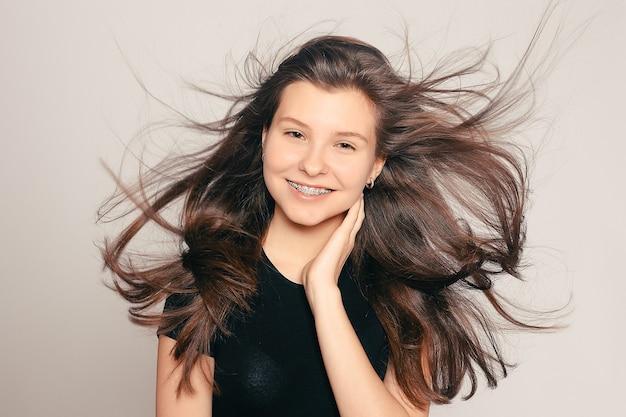 Здоровье, люди, дантист и концепция образа жизни - портрет девочки-подростка, показывающей брекеты. откровенный портрет девушки в подтяжках, с движением волос. смеющаяся девушка в подтяжках, веселый портрет