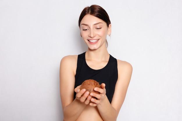 건강, 사람, 음식 및 미용 개념-그녀의 손에 코코넛과 가벼운 자연 메이크업과 완벽한 피부를 가진 아름다운 어린 소녀. 아름다움 얼굴. 흰색 배경에 스튜디오에서 찍은 사진.