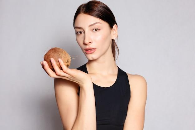 건강, 사람, 음식, 미용 개념 - 가벼운 천연 화장과 코코넛을 손에 들고 완벽한 피부를 가진 아름다운 소녀. 아름다움 얼굴입니다. 흰색 배경에 스튜디오에서 찍은 사진.