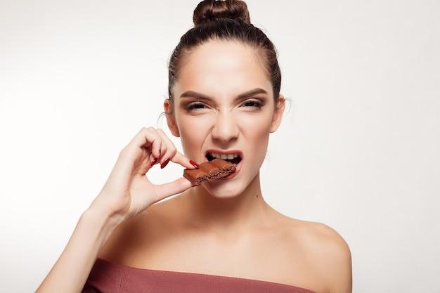 Здоровье, люди, еда и красота концепции - милая улыбающаяся девочка-подросток ест шоколад. девушка сердится и показывает зубы. горизонтальное фото