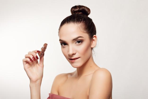 Здоровье, люди, еда и красота концепции - милая улыбающаяся девочка-подросток ест шоколад. девушка прикусывает нижнюю губу. горизонтальное фото