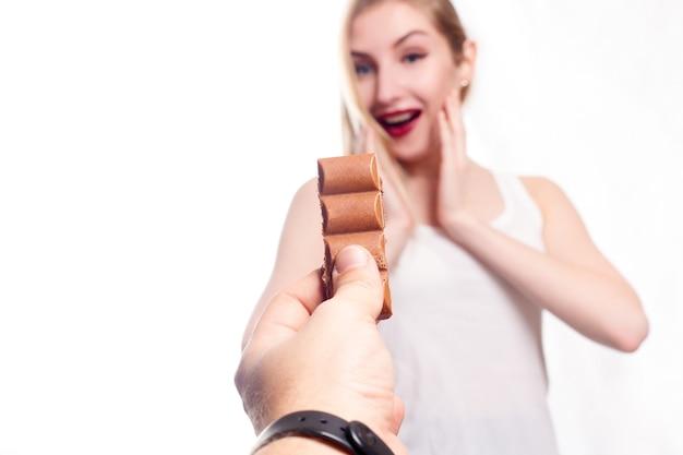 Здоровье, люди, еда и красота концепции - милая улыбающаяся девочка-подросток ест шоколад. девушка удивлена шоколадом. мужская рука с шоколадом