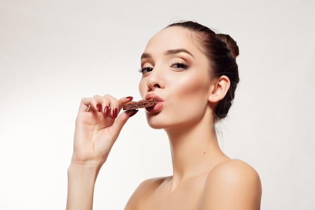 Здоровье, люди, еда и красота концепции - милая улыбающаяся девочка-подросток ест шоколад. горизонтальное фото