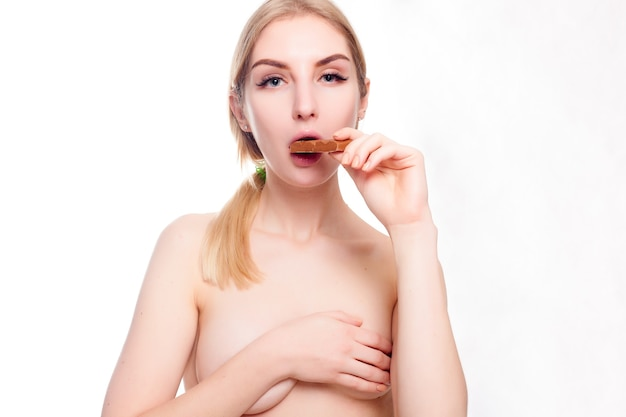 Здоровье, люди, еда и красота концепции - милая улыбающаяся девочка-подросток ест шоколад. портрет красивой женщины, держащей шоколадный батончик.
