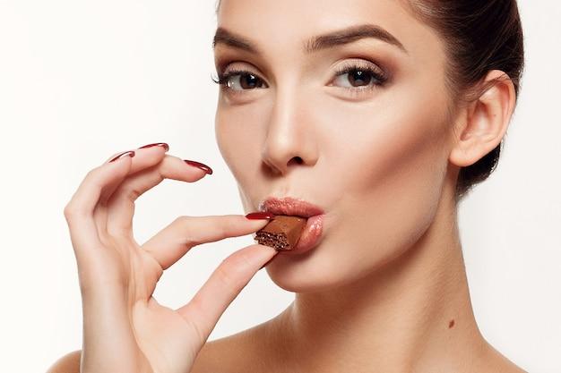 Концепция здоровья, людей, еды и красоты - милая улыбающаяся девочка-подросток ест шоколад