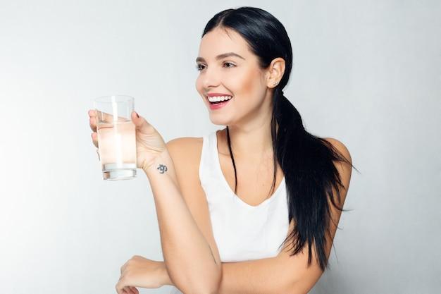 건강, 사람, 음식, 스포츠, 라이프스타일 및 미용 콘텐츠 - 물 한 잔을 들고 웃는 젊은 여성