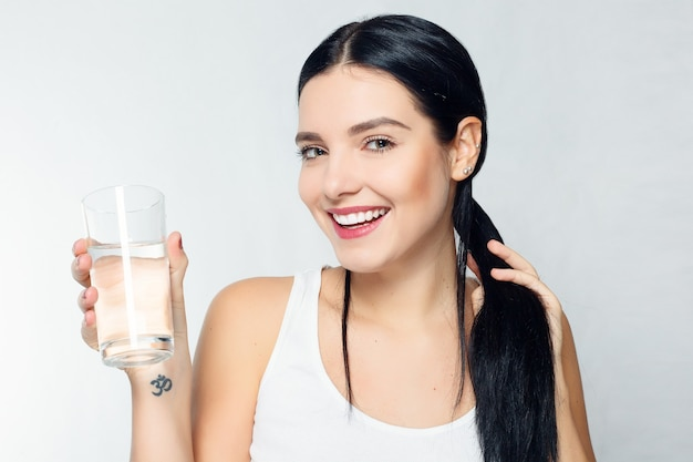 건강, 사람, 음식, 스포츠, 라이프스타일 및 미용 콘텐츠 - 물 한 잔을 들고 웃는 젊은 여성 프리미엄 사진