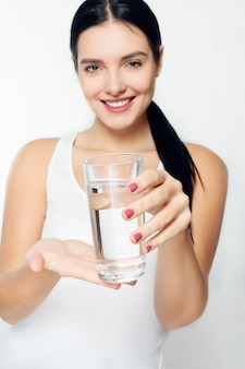 Health, people, food, sports, lifestyle and beauty content - smiling young woman with glass of water. cup out of focus, woman in the background