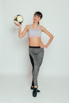 Здоровье, люди, спорт и концепция образа жизни - молодая и сексуальная девушка с футбольным мячом на белом фоне. выстрел из спортивной молодой женщины. активный образ жизни, хорошее самочувствие.