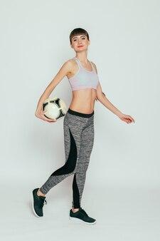 건강, 사람, 스포츠 및 라이프 스타일 개념-흰색 표면 위에 축구 공을 가진 젊고 섹시한 여자