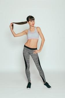 건강, 사람, 스포츠 및 라이프 스타일 개념-회색 표면에 스튜디오에서 스포티 한 몸매를 가진 젊은 행복 피트니스 소녀