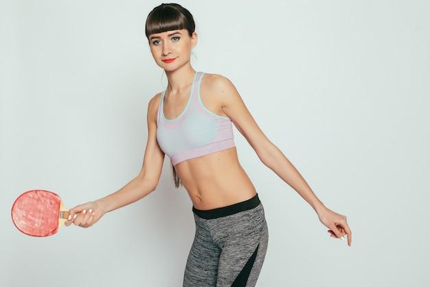 건강, 사람, 스포츠 및 라이프 스타일 개념-탁구 라켓과 공을 들고 젊은 여자. 회색 배경에 스튜디오에서 스포티 한 시체와 함께 젊은 행복 피트니스 소녀.