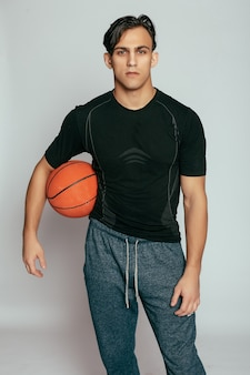 Health, people, sport and lifestyle concept - real player. handsome young smiling man carrying a basketball ball and looking at camera while standing against grey background