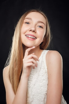 Health, people, youth, dental and beauty concept - portrait of teen girl showing dental braces.