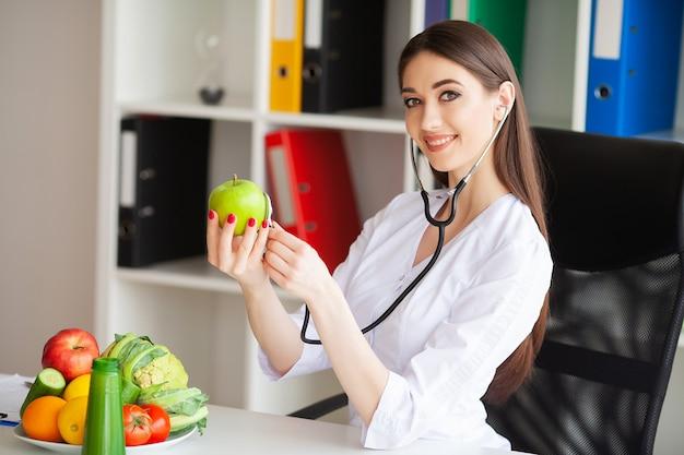 Здоровье. портрет счастливого диетолога в светлой комнате. держит зеленое яблоко и сантиметровую ленту. здоровое питание. свежие овощи и фрукты на столе