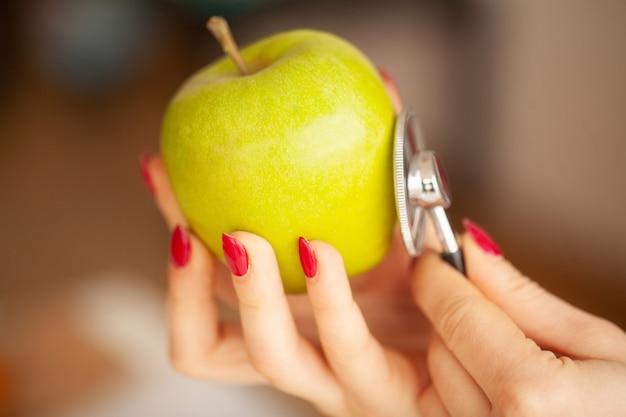 健康。明るい部屋で幸運な栄養士の肖像。青リンゴとセンチメートルのリボンを保持します。健康的な栄養。テーブルの上の新鮮な野菜や果物