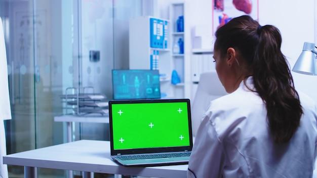 医療従事者は、白衣を着た私立クリニックでクロマキー付きのラップトップを使用し、青い制服を着た看護師がコンピューターで患者の結果をチェックしています。