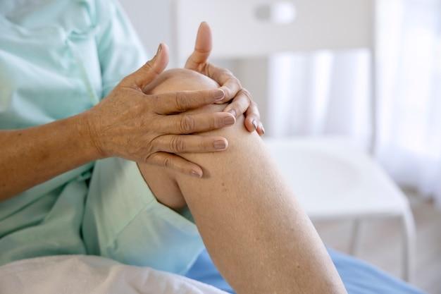 Концепция проблемы со здоровьем старая женщина страдает от боли в колене в больнице