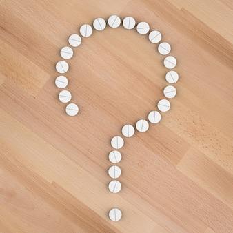 白い錠剤の健康問題の概念は疑問符を配置します