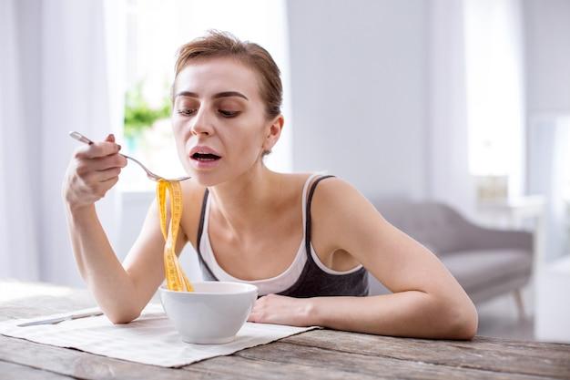Проблемы со здоровьем. приятная молодая женщина пытается есть, страдая от анорексии