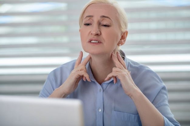 Health, problems. serious fair-haired woman in front of laptop monitor hands near neck showing lymph nodes with fingers.