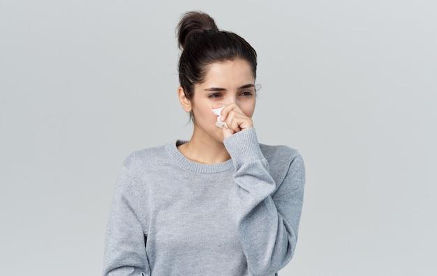 健康上の問題ナプキン鼻水灰色の背景を持つ若い女性。高品質の写真