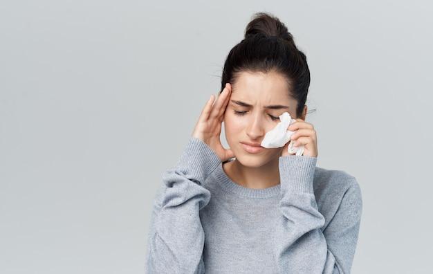 Молодая женщина проблем со здоровьем с салфеткой насморк болезни сером фоне. фото высокого качества