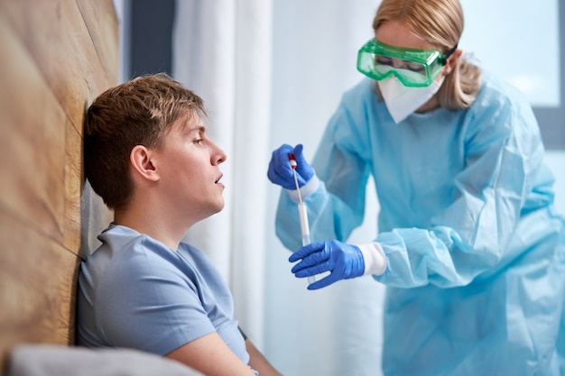 Ppeスーツの医療専門家は、ベッドに横たわっている自宅の若い男性患者に鼻と喉の綿棒を導入します。コロナウイルスパンデミック中の鼻腔培養サンプリングを分析するための迅速抗原検査キット。