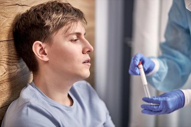 ベッドに横たわっている自宅の若い病人患者に鼻と喉の綿棒を導入するppeスーツの医療専門家。コロナウイルスパンデミック中の鼻腔培養サンプリングを分析するための迅速抗原検査キット。
