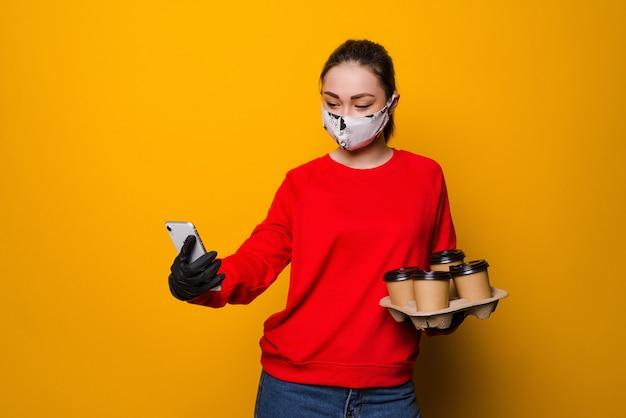 健康保護、安全性およびパンデミックの概念。配達アジアの女性は、黄色の壁に使い捨ての持ち帰り用コーヒーカップを保持している顔の保護マスクと手袋で電話を使用します