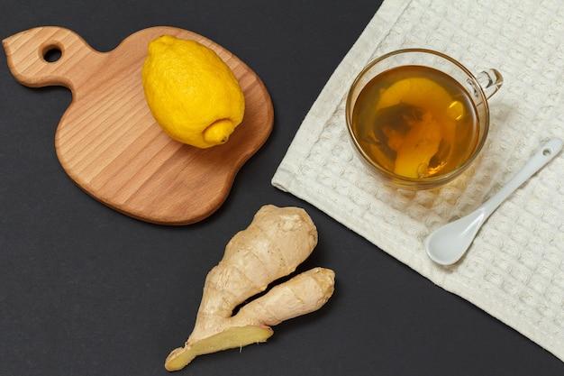 風邪やインフルエンザの緩和のための健康治療食品。お茶とレモンのカップ、黒の背景に生姜。上面図。免疫システムを高める食品。