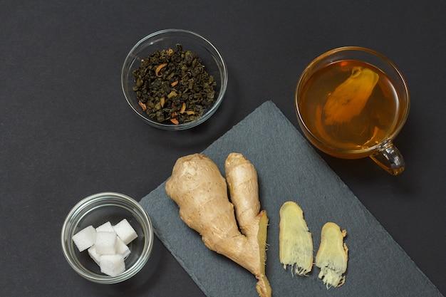 黒の背景に生姜とお茶を使った風邪やインフルエンザの緩和のための健康治療食品。上面図。免疫システムを高める食品。