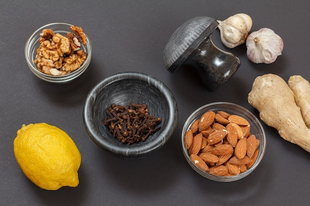 黒の背景にレモン、ニンニク、アーモンド、生姜、クルミを使った風邪やインフルエンザの緩和のための健康療法食品。上面図。免疫システムを高める食品。