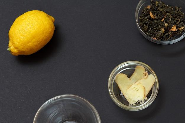 黒の背景にレモン、生姜、緑茶を使った風邪やインフルエンザの緩和のための健康療法食品。上面図。免疫システムを高める食品。