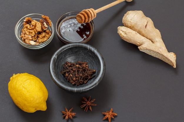 黒の背景にレモン、生姜、蜂蜜、アーモンド、クルミを使った風邪やインフルエンザの緩和のための健康療法食品。上面図。免疫システムを高める食品。