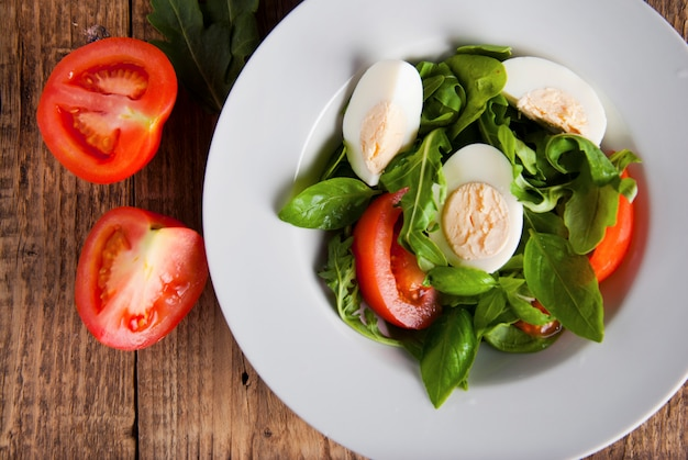 Health salad with boiled eggs, tomato, lettuce, arugula and spinach.