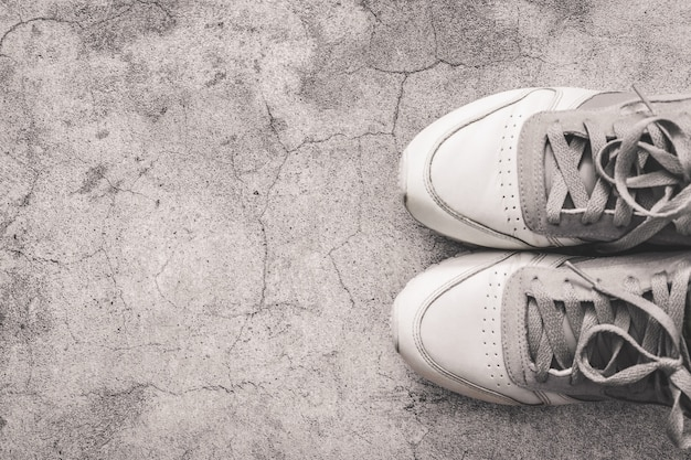 Health and sport concept. top view of gray sneakers on a concrete table with copy space