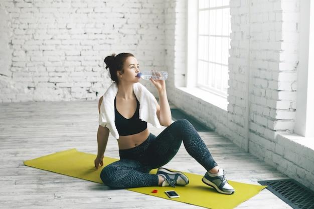 健康、スポーツ、フィットネス、ダイエット、減量のコンセプト。美しい若いブルネットの女性は、物理的なトレーニングの後、タオルで汗を拭き、マットの上に座って、ペットボトルから新鮮な水を飲みます