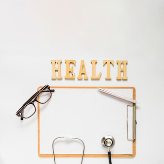 Health text near the clipboard with eyeglasses; stethoscope and pen on white background