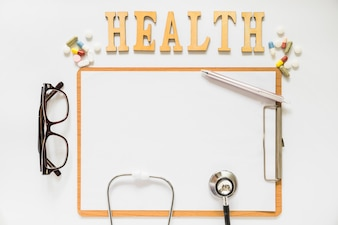 Health text with pills over the clipboard with paper; eyeglasses; pen and stethoscope