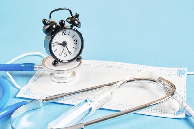 건강 시간 의료 개념. 파란색 배경 복사 공간에 청진기와 알람 시계 얼굴 마스크 앰플 주사기