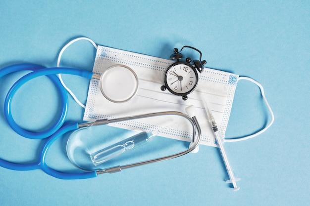 건강 시간 의료 개념. 파란색 배경 상위 뷰에 청진기와 알람 시계 얼굴 마스크 앰플 주사기