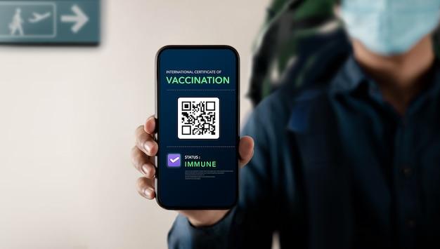 코로나바이러스 또는 코비드-19에 대한 건강 백신 여권. 공항에서 인증된 국제 여행에 면역 상태의 예방 접종을 받은 휴대전화 화면을 제시하는 여행자