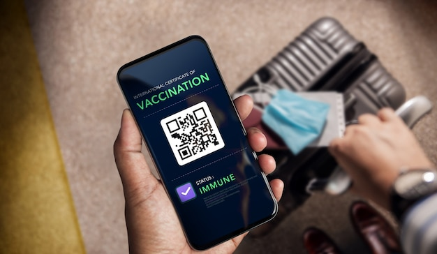 코로나 바이러스 또는 covid-19에 대한 건강 백신 여권. 면역 상태의 예방 접종을받은 휴대 전화를 사용하여 공항에서 국제 여행 인증을받은 여행자