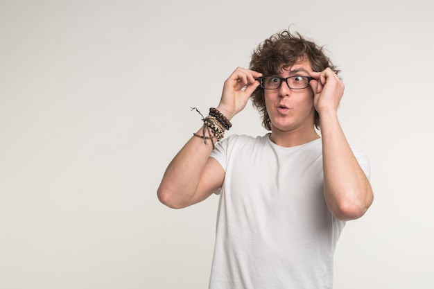 Health, vision problems and people concept. student man wearing eye glasses on white background