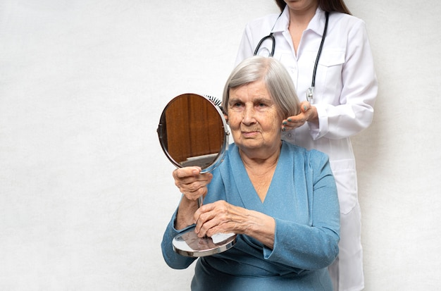 Санитарка делает прическу для пожилой женщины.