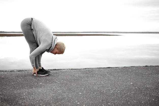 健康、幸福、活動の概念。スニーカーとスポーツ服を着て屋外で体操をし、前屈のヨガのポーズで湖でポーズをとるフィットショートヘアの女性のフルレングスショット