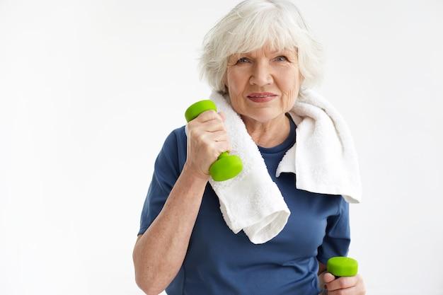 건강, 웰빙, 활동, 성숙도 및 연령 개념. 그녀의 목에 흰 수건으로 실내에서 은퇴 훈련에 낙관적 인 노인 여성, 녹색 아령 쌍으로 운동하고 웃고